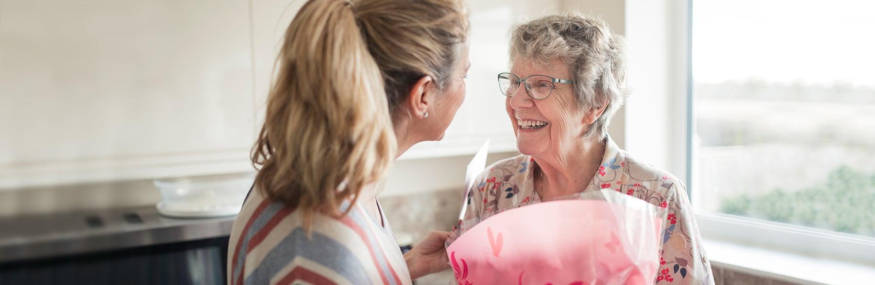 Caregiver bringing flowers to senior client