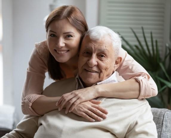 Girl hugging elderly man