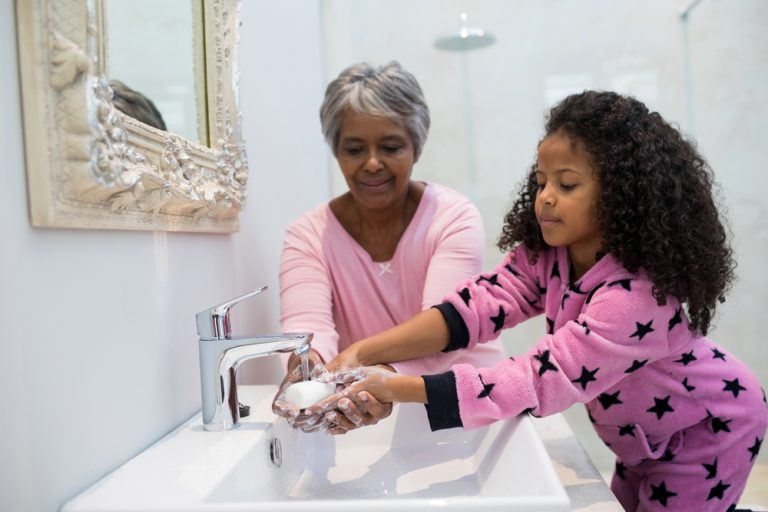 Grandmother and granddaughter washing hands with soap in bathroom sink
