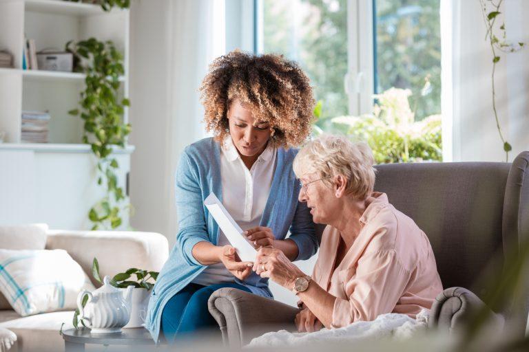caregiver helping senior read a piece of paper