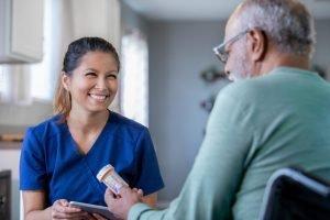 professional caregiver helping senior with medicine